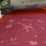 Applying red ink to card stock.